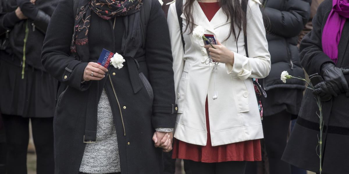 Two women holding hands and flowers