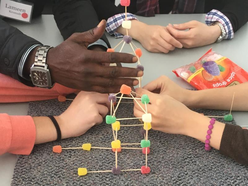 close-up of diverse hands working together at interpersonal leadership program