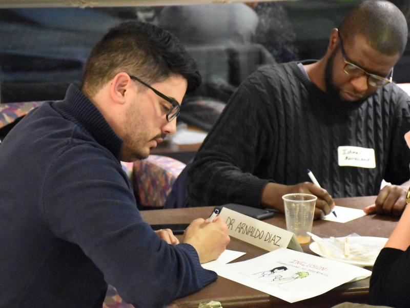 Two men writing at teach-in workshop